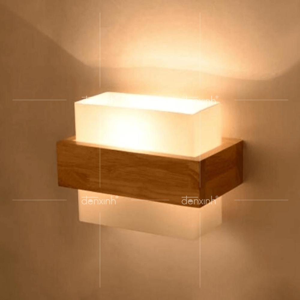 Đèn áp tường khối vuông đai gỗ của Đèn Xinh mang lại nguồn ánh sáng ấm áp cho mảng tường ngoài trời